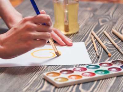 a hand painting a picture with watercolors